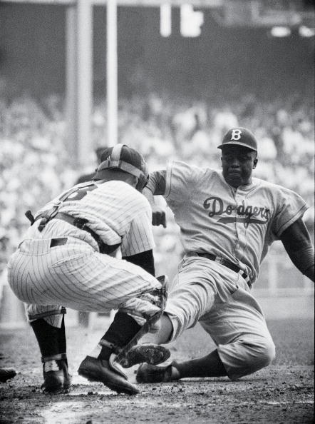 16. Jackie Robinson steals home in Game 1 of the 1955 World Series; Yogi Berra still contests the call; Frank Hurley, New York Daily News.