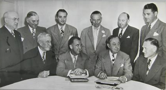 "Men of the 1945 PCL: (L-R, back): Bill Keppler, Portland; Don Stewart, Sacramento; Los Angeles Angels; Yubi Separovich, Sacramento; Emil Sick, Seattle; Victor Ford Collins, Hollywood; Bill Starr, San Diego. Seated: Charles Graham, San Francisco; Commissioner A.B. ""Happy"" Chandler, PCL President, Clarence Rowland; Clarence ""Brick"" Laws, Oakland."